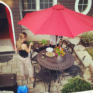 backyard patio and patio furniture with large red umbrella on a paver patio